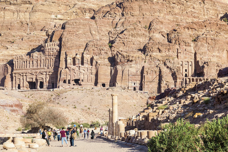 PETRA, JORDAN - OCTOBER 28, 2014: Unidentified locals and tourists on colonnaded street with urn, silk and royal tombs on background.