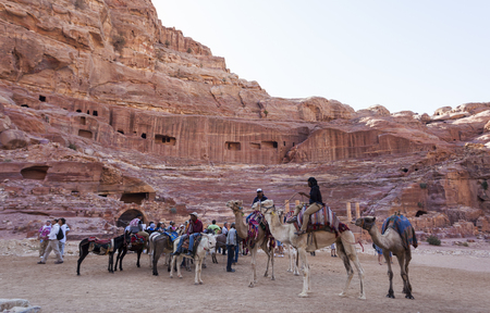 PETRA, JORDAN - OCTOBER 28, 2014: Unidentified tourists and local camel riders in front of ruins of Roman amphitheatre.