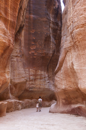 PETRA, JORDAN - OCTOBER 29, 2014: Unidentified tourists in the Siq - natural narrow passageway to Petra Editorial