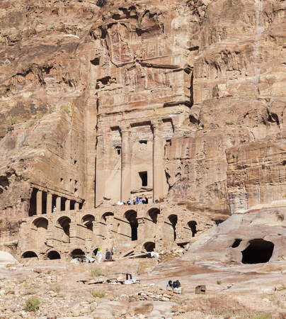 PETRA, JORDAN - OCTOBER 28, 2014: Unidentified tourists near Urn Tomb one of the best preserved tombs hewn into the sandstone cliff.
