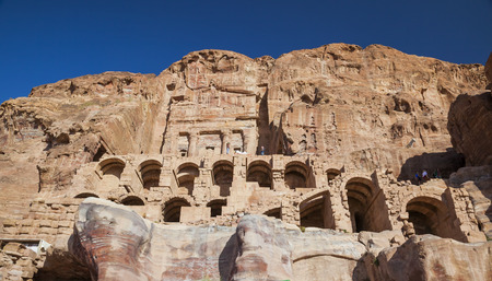 urn: PETRA, JORDAN - OCTOBER 28, 2014: Unidentified tourists near Urn Tomb one of the best preserved tombs hewn into the sandstone cliff.