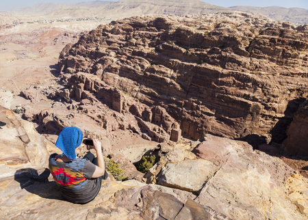 Women takes photo from the cliff edge of High Place of Sacrifice. Petra. Jordan. Stock Photo