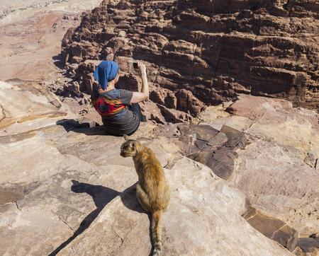 sacrifice: Mujeres (con el gato en el primer plano) toma la foto del borde del acantilado de alto lugar del sacrificio. Petra. Jordán.
