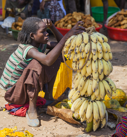 NEAR KONSO, OMO VALLEY, ETHIOPIA - JANUARY 3, 2014: Unidentified women from Konso tribal area sell bananas at local village market