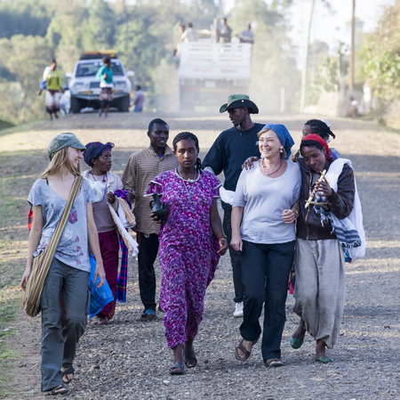 HAYZO VILLAGE, DORZE, OMO VALLEY, ETHIOPIA - JANUARY 3, 2014: Unidentified western tourists surrounded by Local Dorze people. Editorial