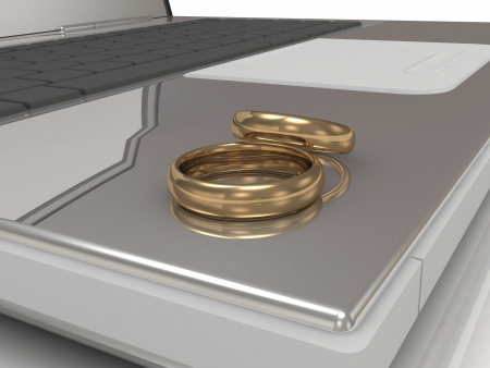 Two wedding rings on a laptop on a white background Stock Photo - 14618656