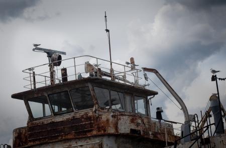wheelhouse: Wheelhouse old rusty ship on the river with seagulls on masts Stock Photo