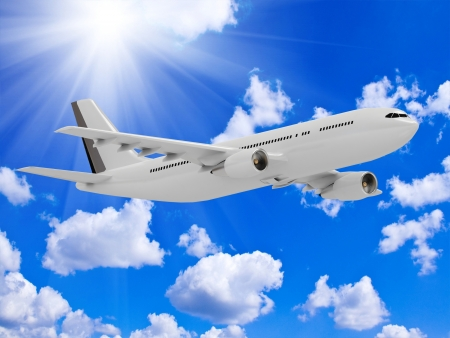 White passenger airliner flies under the bright sun in the blue sky above the clouds Stock Photo