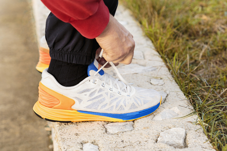 mid distance: Focus on a side view of two human hands reaching down to a white orange blue athletic shoe at the end of an ankle being supported by a rock with the sun shining at sunset