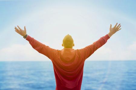 hombre rojo: Vista trasera del hombre extendiendo los brazos y mirando el océano