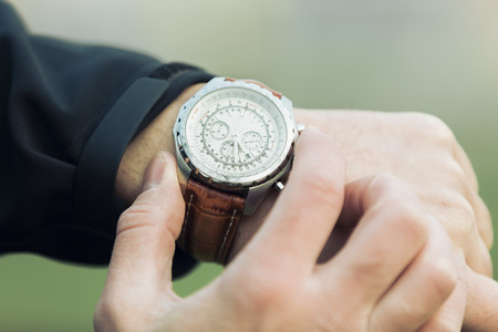 Man hand with elegant expensive watch with leather brown strap. In background is green blurred natural green colour in park