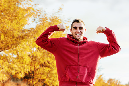 sholders: young athlete after running flexing muscles rising up his hands above sholders and smiling while looking at camera. Stock Photo