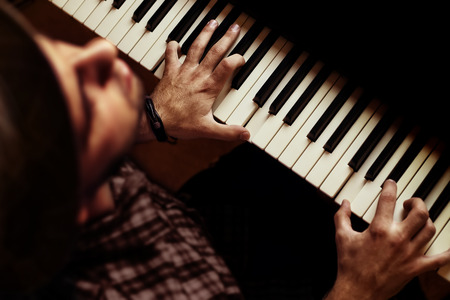 Man singer and performer singing with his eyes closed while playing piano on dramatic stage. Photo shot from above angle over singers had with keyboard and hands in focus with shallow depth of field. Imagens