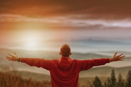 atmosfera: Hombre con los brazos abiertos mirando las montañas foto viva con capas de montañas, valles delante. El hombre tiene la espalda frente a la cámara con las montañas en el fondo y el efecto sunflare
