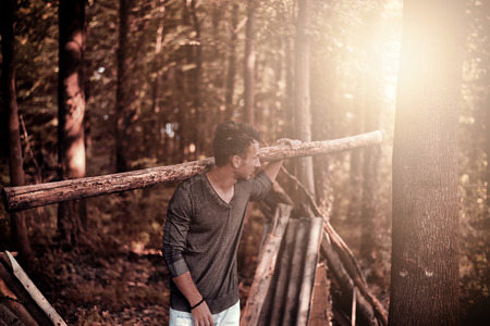 shoulder carrying: Young handsome man carrying heavy log on his shoulder as a survivor at the forest. He is looking aside over his shoulder while the forest is in background and sun rising from behind.