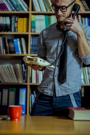 Handsome man standing and talking on the phone at library while computer and coffee cup is in front of him and bookshelves at background. Stock Photo