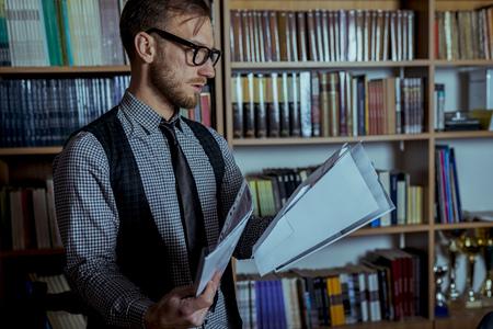 Student durchläuft seine Dokumente in der Bibliothek im Hintergrund. Standard-Bild - 75287797
