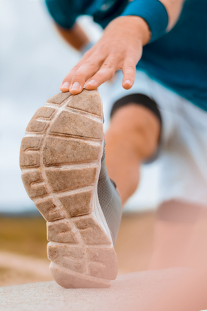 Athlete is Stretching Outdoors. Closeup shot of his out-sole. Standard-Bild - 108753372