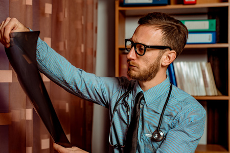 Doctor Observing X-Ray at his Office. Dramatic scene vivid contrast colors Standard-Bild - 116002464