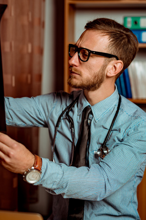 Doctor Observing X-Ray at his Office. Dramatic scene vivid contrast colors Standard-Bild - 116002468