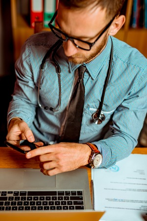 Doctor Observing X-Ray at his Office and using the smartphone. Dramatic scene vivid contrast colors Standard-Bild - 116002574
