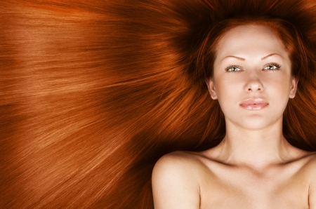 fashion concept portrait of a woman with beautiful long red healthy shiny hair photo