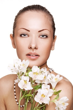 sensual young woman with perfect clean skin holding flowers photo