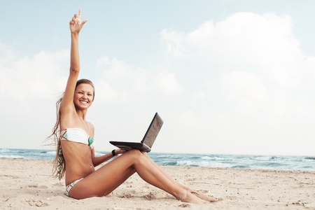 Sexy beautiful woman in bikini using laptop at the beach photo