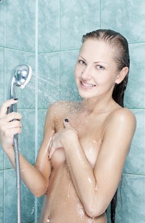 mujer desnuda de espalda: sexy y feliz joven y bella mujer tomando una ducha Foto de archivo