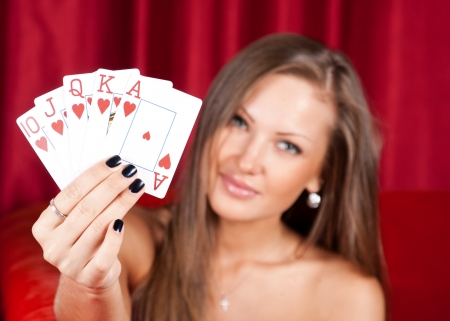 beautiful young woman holding poker cards photo