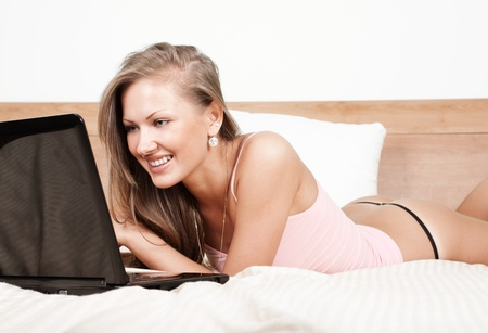 lying in bed: Happy girl lying in bed with laptop Stock Photo
