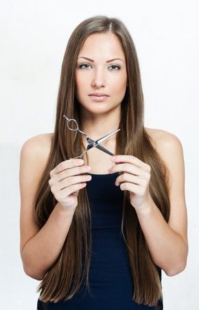 woman with long hair holds scissors