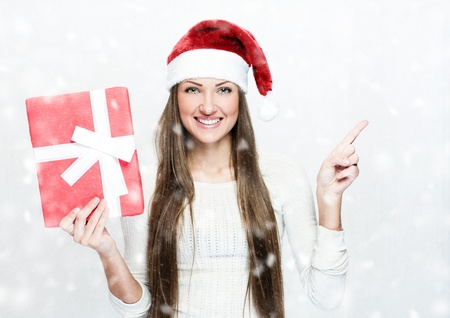 young smiling woman in santa hat , holds christmas gift , snow Stock Photo - 16467547