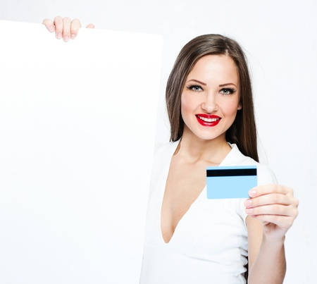 smiling young beautiful woman holding blank board and credit card photo