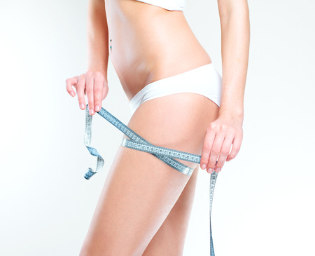 허리의 잘룩 한 선: 그녀의 허리를 측정하는 여자 스톡 사진