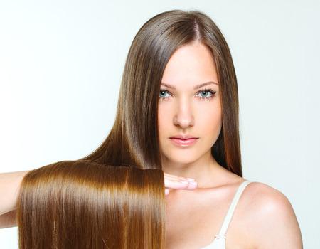 cabello lacio: Close-up retrato de una bella joven con el pelo largo y brillante de color marrón. atractiva chica con cabello largo saludable. pelo natural. Foto de archivo