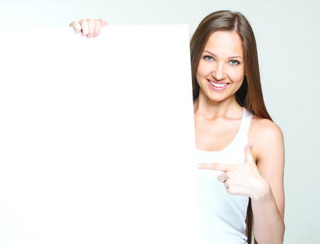 smiling happy woman standing and holding big blank paper. Stock Photo - 28215270