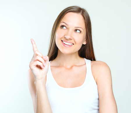 close-up portrait of a smiling beautiful woman pointing her finger on the blanck space. woman got an idea.