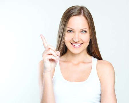 close-up portrait of a smiling beautiful woman pointing her finger on the blanck space. woman got an idea. Stock Photo - 28215276