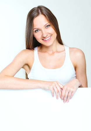 smiling happy woman standing and holding big blank paper. Stock Photo - 28215277