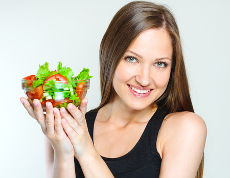 vegs: sporty attractive woman eating vegetables salad. healthy food. slim girl. Stock Photo