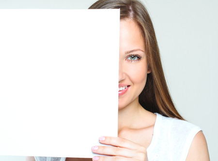one sheet: smiling happy woman holding  blank paper  empty copyspace for ads  Stock Photo
