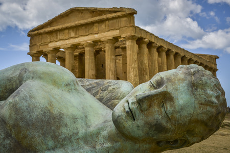 agrigento: bronze statue of fallen ikaro on the background the concorde temple, Agrigento, Sicily, Italy
