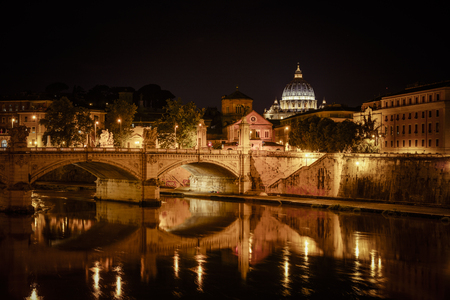 basillica: Basilica of San Pietro at night overlooking the Tevere river and surrounding historical landmarks of Rome. Stock Photo
