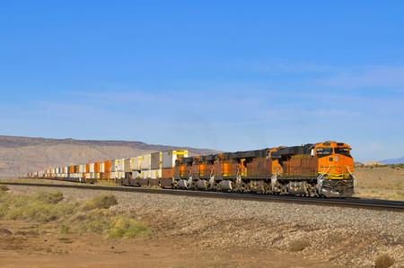 goederentrein met vier locomotieven en wagons vol met containers in de woestijn, Arizona, VS. Stockfoto