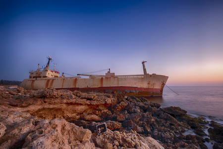 accidental: Seascape: famous boat, shipwrecked near the rocky shore at the sunset. Mediterranean, near Paphos. Cyprus.