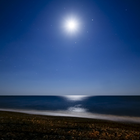 midnight: bright moon surrounded with stars reflected in the water at the beach at night