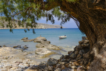 tied in: small boat was tied with a rope to the rock on a small beach in the summer on the island of Crete Greece Stock Photo