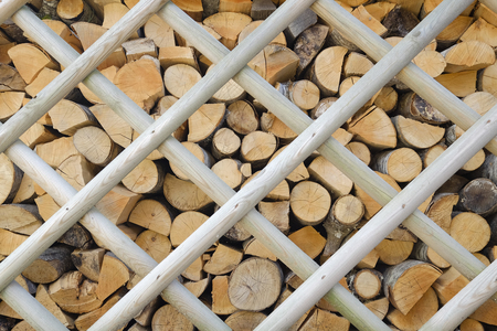 neatly stacked: background of a pile of firewood neatly stacked behind a wooden fence