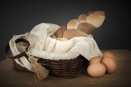 3 types interwoven bread in a wicker basket beside a few eggs on a wooden table